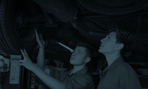 young men fixing a car