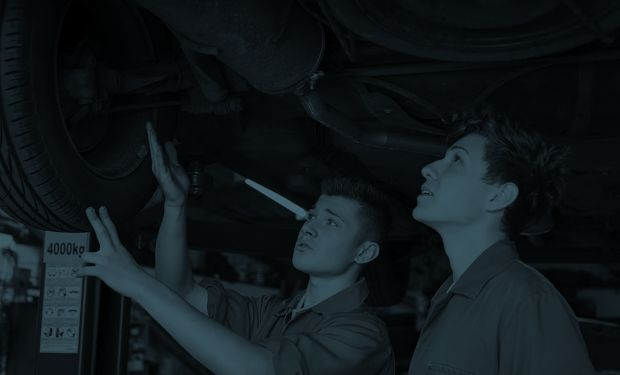 young men fixing a car
