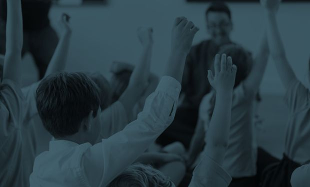 Children with hands up in class