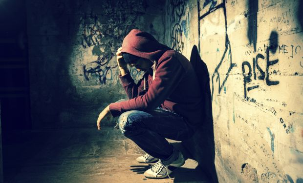 Young man sat against a wall in a dark alley