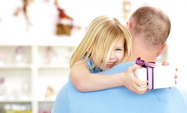 Happy little girl holding a present while cuddling her dad