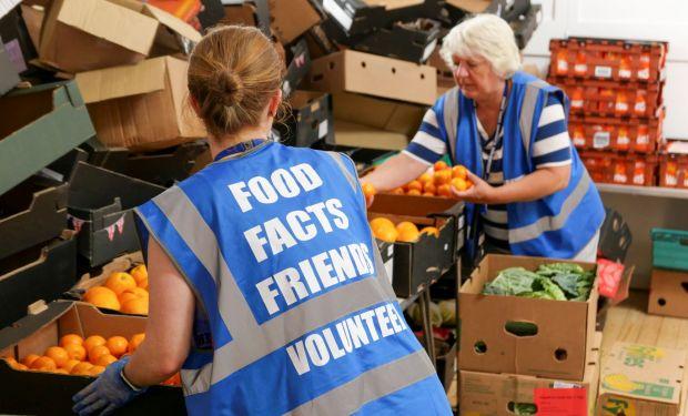 Two volunteers unpack fruit at a foodbank in Scotland