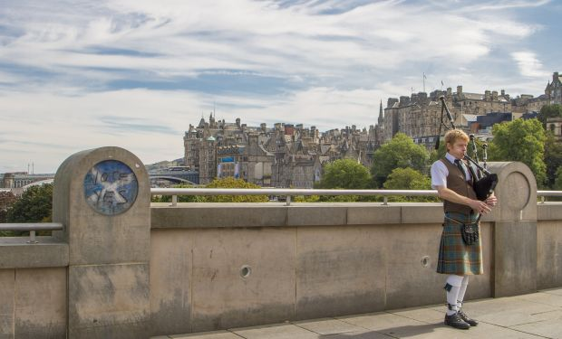 Man playing bagpipes on bridge in Scotland