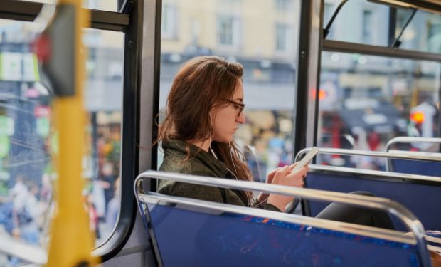 Young woman with smartphone on bus