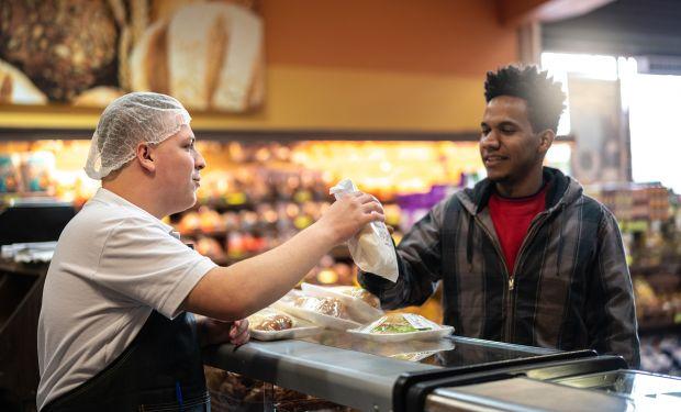 Supermarket worker serving a customer