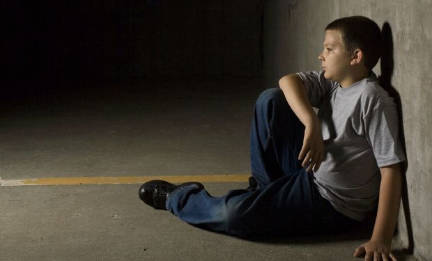 Lonely boy sitting against a wall in a dark room