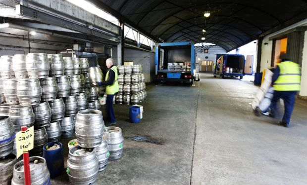 Factory workers moving kegs