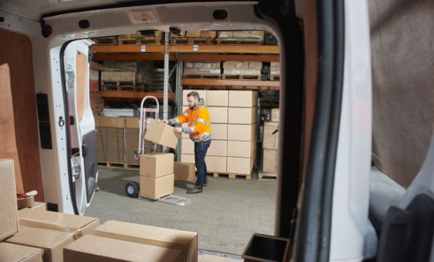 Delivery driver loading boxes into van