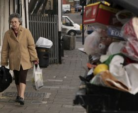 Woman walking past an over filled bin