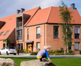 A young boy plays on a rock at Derwenthorpe