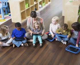 Children sat down on the floor with a teacher learning on tablet PCs