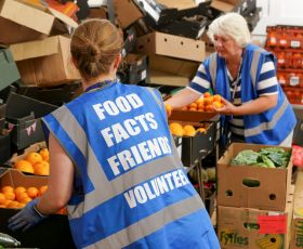 Two volunteers unpack fruit at a foodbank in Scotland