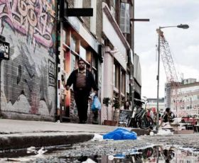 Man walking down run down street covered with graffiti and rubbish