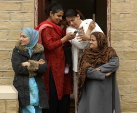Women stand chatting in a doorway