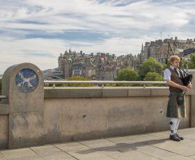 Man playing bagpipes on bridge in Scotland