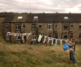 A woman pegging clothes on a clothesline