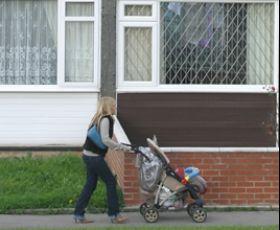 Mum pushing pram down the street