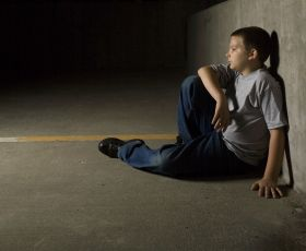 Lonely boy sitting against a wall in a dark room