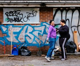 Two women laugh during a neighbourhood clean up