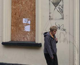 Man walking past boarded up rundown building