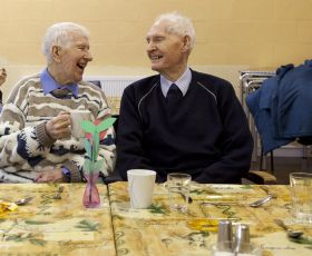 Two older men share a joke