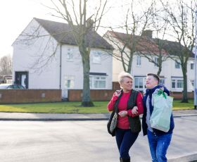 Mum and disabled son walk down a residential street