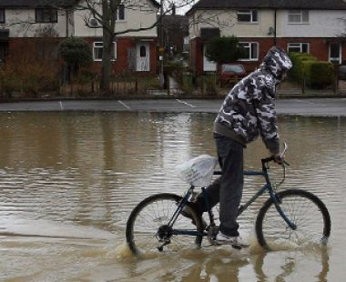 Youth riding a bike through flood waters