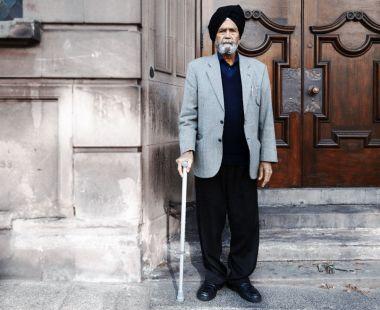 Older Asian man with walking stick stood in doorway