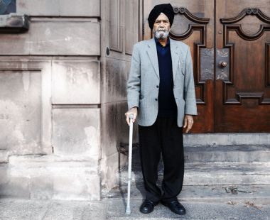 Older Asian man with walking stick stood in doorway