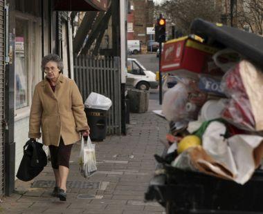 Woman walking past an over filled bin