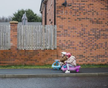 Two young children racing each other in toy cars