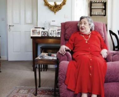 Elderly lady in an armchair talking to a carer