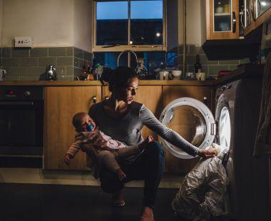 Parent putting washing in a washing machine