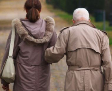 Young and old person walking arm in arm