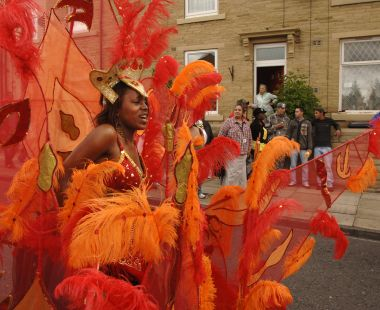 Woman in carnival outfit parading down the street