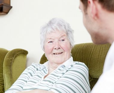 An older woman speaking to a younger man