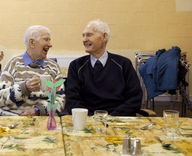 Two older men share a joke
