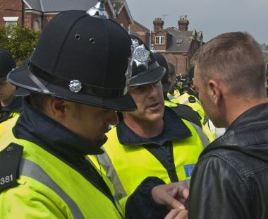 Police officers speak to a man