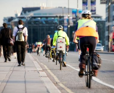 cyclists riding and people walking